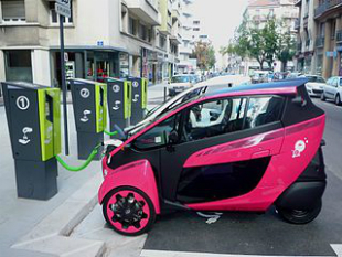 A Toyota I-Road at a charging station