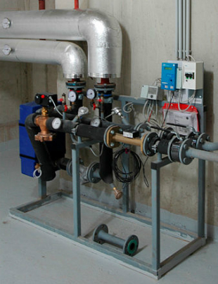 A district heating substation in a residential neighborhood with a thermal capacity of 300 kW. Two components of the heat meter are visible: the metering electronics unit, and the ultrasonic flow meter.